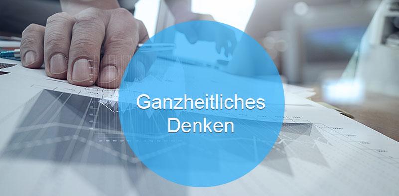 Das Bild zeigt eine Hand, die für Data Sciences auf einem Analyzer arbeitet. Der Text darauf: Ganzheitliches Denken.